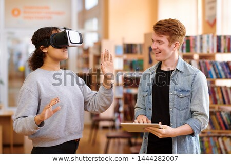 Happy student with tablet interacting with his classmate with vr headset Stock photo © pressmaster