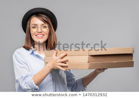 happy girl in hat shirt and eyeglasses holding stack of thin carton packages stock photo © pressmaster