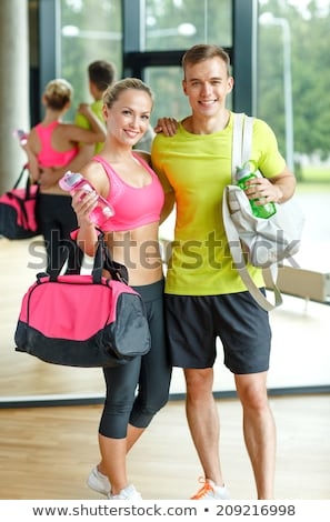sportive couple with water bottles and bag in gym Stock photo © dolgachov
