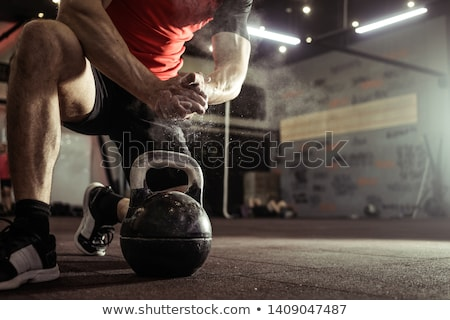 Stock photo: Young man lifting at a crossfit gym