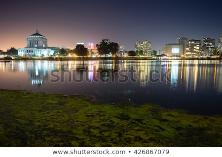 Oakland skyline panoramic view with Lake Merritt Reflections at blue hours Stock photo © yhelfman
