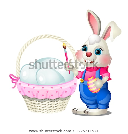 Cheerful Easter bunny with a brush in his paws and a basket of chicken eggs isolated on white backgr stock photo © Lady-Luck