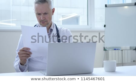 Doctor reading on a document report and writing on paperwork and Stock photo © snowing