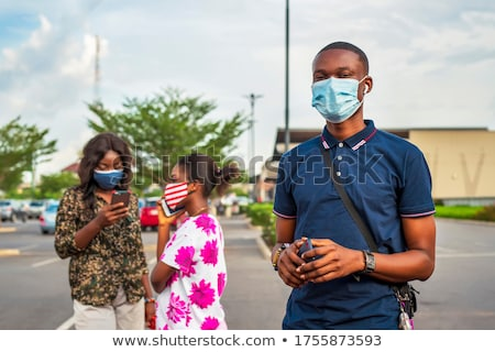 Travel and technology. Young man in medical mask tourist with the flag of Malaysia is looking at a c Stock photo © galitskaya