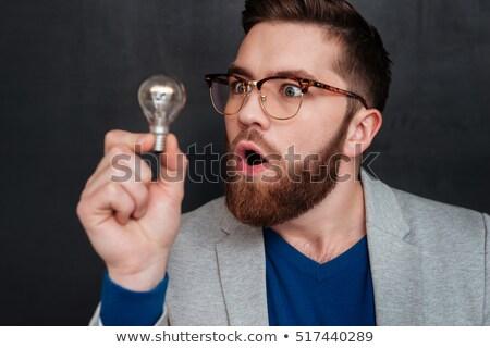 Zavart férfi szemüveg tart villanykörte kezek Stock fotó © feelphotoart