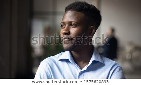 Closeup portrait of a young african-american businessman on dark background Stock photo © deandrobot