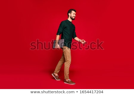 full length of smiling young businesman with laptop stock photo © deandrobot