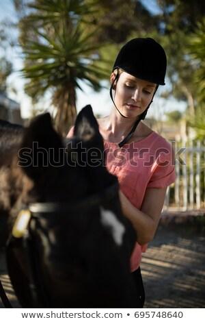 Сток-фото: женщины · жокей · глядя · вниз · Постоянный · лошади · сарай