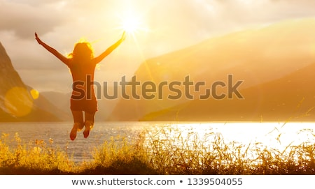 Woman jumping in field Stock photo © IS2