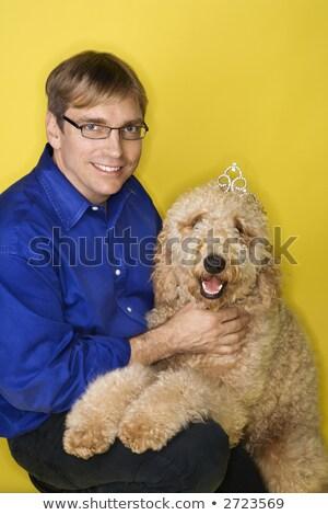 Сток-фото: Man Holding Dog Wearing Tiara