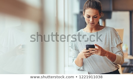 woman checking messages on her cell phone stock photo © alexeys