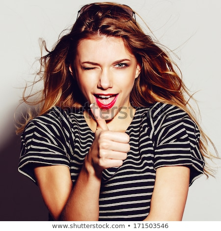 Pretty young smiling woman showing okay gesture. Stock photo © deandrobot