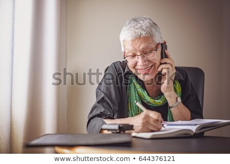 Mature woman taking a phone call from home office Stock photo © IS2
