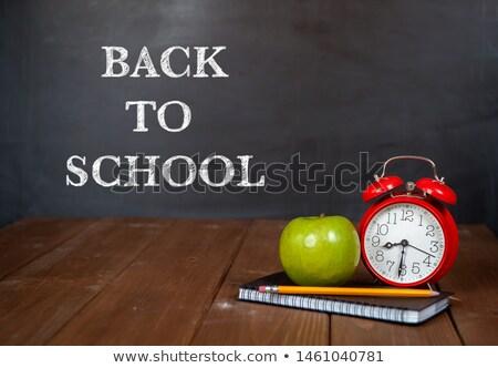 School supplies by alarm clock on wooden table against black board Stock photo © wavebreak_media