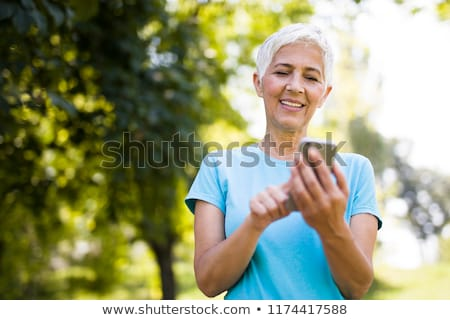 Stockfoto: Sporty Senior Woman Using Mobile Phone In The Park