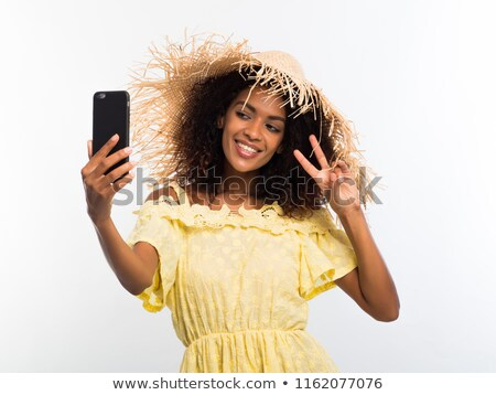 happy elegant woman in dress and straw hat making selfie stock photo © deandrobot