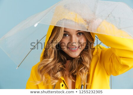 Image of positive woman 20s wearing yellow raincoat holding mobi Stock photo © deandrobot