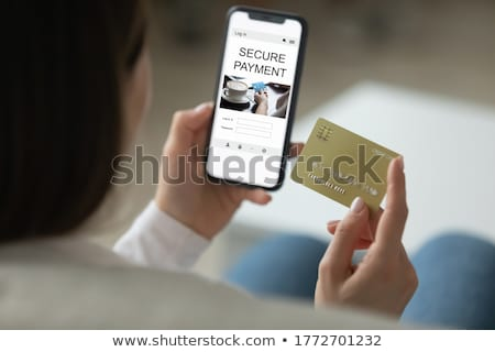 Image of pleased woman holding mobile phone and credit card in h Stock photo © deandrobot
