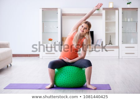 smiling woman practicing yoga on fitness ball stock photo © kzenon
