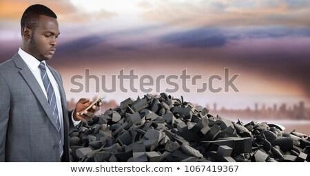 broken concrete stone pile and businessman on phone in cityscape stock photo © wavebreak_media