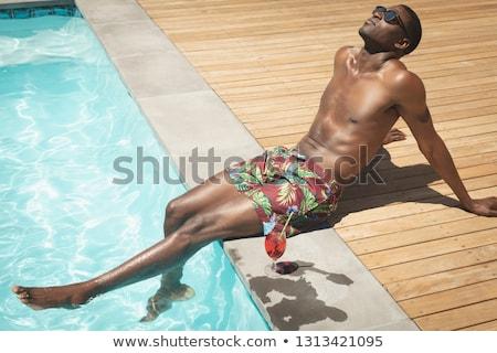 Widok z boku młodych człowiek posiedzenia podwórko Zdjęcia stock © wavebreak_media