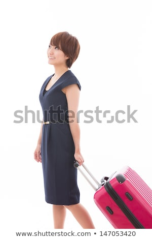 Young Asian female business traveler with suitcase standing by elevator door Stock photo © pressmaster