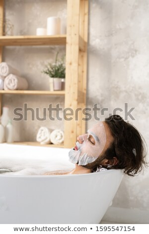 Relaxed young man having face mask while lying in bath with hot water and foam Stock photo © pressmaster