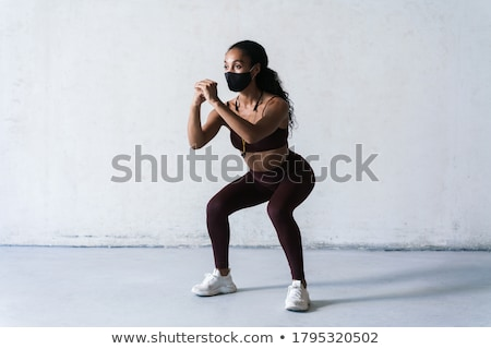 Image of focused african american sportswoman doing exercise Stock photo © deandrobot