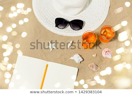 notebook, cocktails, hat and shades on beach sand Stock photo © dolgachov