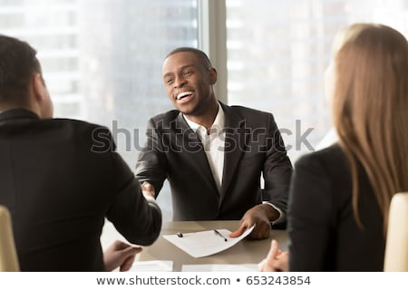 Attractive man in business suit with acceptance sign sitting at  Stock photo © HASLOO