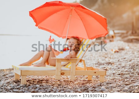 Girl lying on deckchair with lollipop  Stock photo © deandrobot