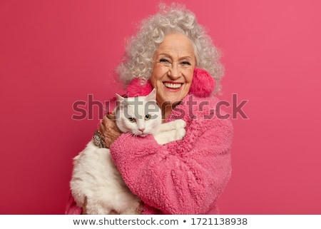 Stock photo: Smiling aged woman with cat on hands
