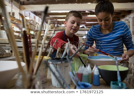 Female potter and boy painting bowl Stock photo © wavebreak_media