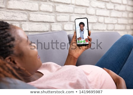 A young woman lying on her couch talking on the phone stock photo © monkey_business