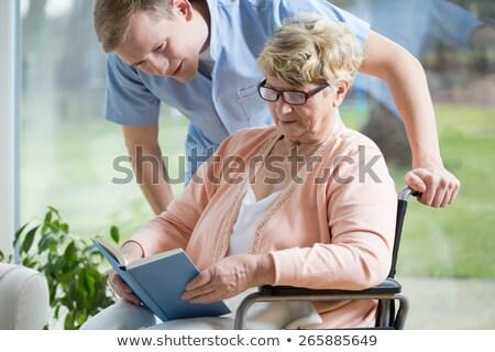 Pielęgniarki czytania książki niepełnosprawnych starszy człowiek Zdjęcia stock © AndreyPopov