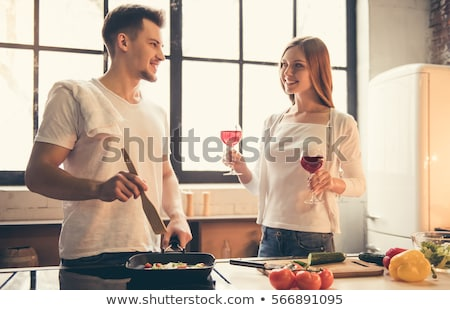 couple cooking food and drinking wine at home stock photo © dolgachov