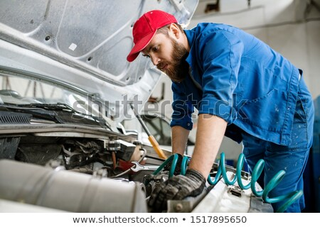 young bearded technician of repair service examining broken engine of lorry stock photo © pressmaster