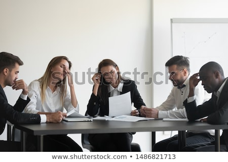 upset businesswoman sitting with colleague in meeting stock photo © andreypopov