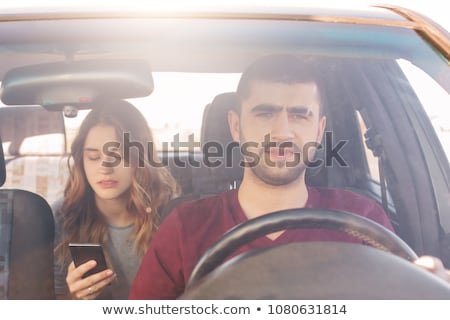 couple with smartphones riding on back seat of car stock photo © dolgachov