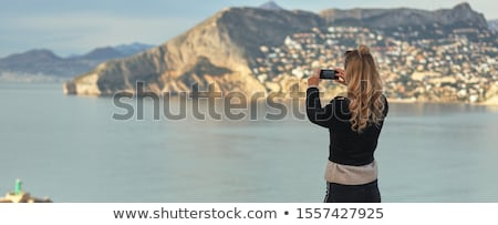 Rear view woman holding smartphone take photography of mountains Stock photo © amok