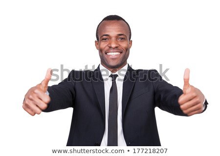 Young man with toothy smile showing thumbs up while standing in isolation Stock photo © pressmaster