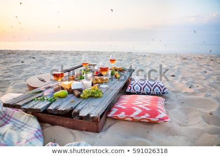 Picnic on the beach at sunset in the style of boho Stock photo © dashapetrenko
