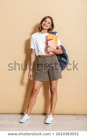 Image of lovely teen girl carrying backpack holding exercise boo Stock photo © deandrobot