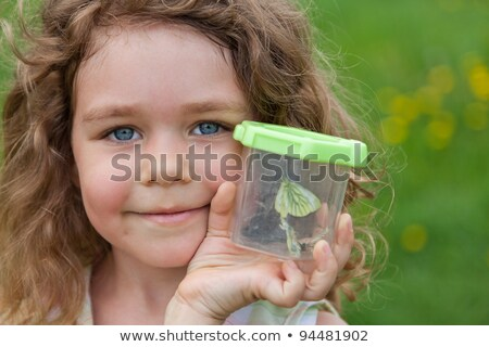 Little girl holds the container with the caught butterfly Stock photo © Lopolo