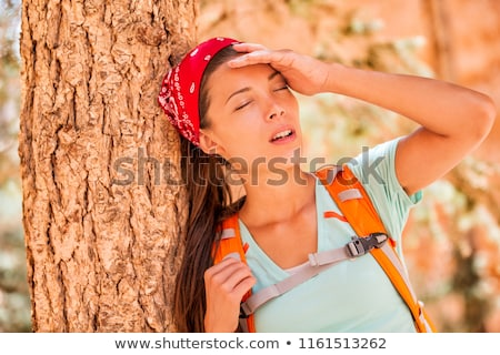 Dehydrated tired hiking woman thirsty feeling exhausted heat stroke. Girl with headache from hot tem Stock photo © Maridav
