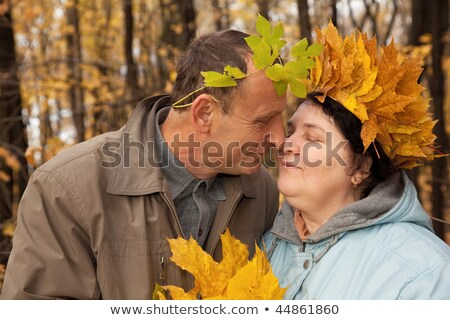 Old man and old woman with wreath of maple leaves embrace in autumnal forest Stock photo © Paha_L