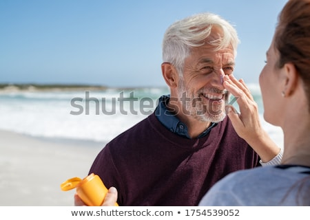 Man looking at woman applying sunblock Stock photo © IS2