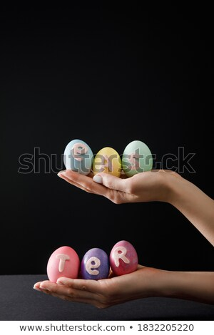 cropped view of woman holding painted easter eggs in hands isolated on yellow stock photo © lightfieldstudios