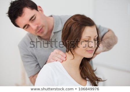 woman sitting while being massaged by a man in  room Stock photo © Lopolo
