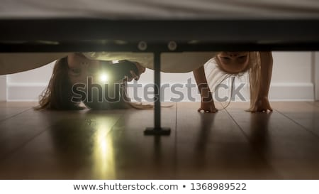 Little Girl Looking Under The Bed With Flashlight Stock photo © AndreyPopov
